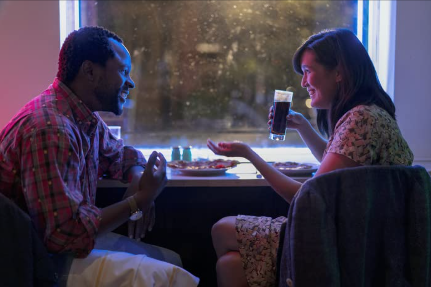 """Man and woman look into each other's eyes while laughing at a diner in Modern Love's """"The Night Girl Finds a Day Boy"""""""